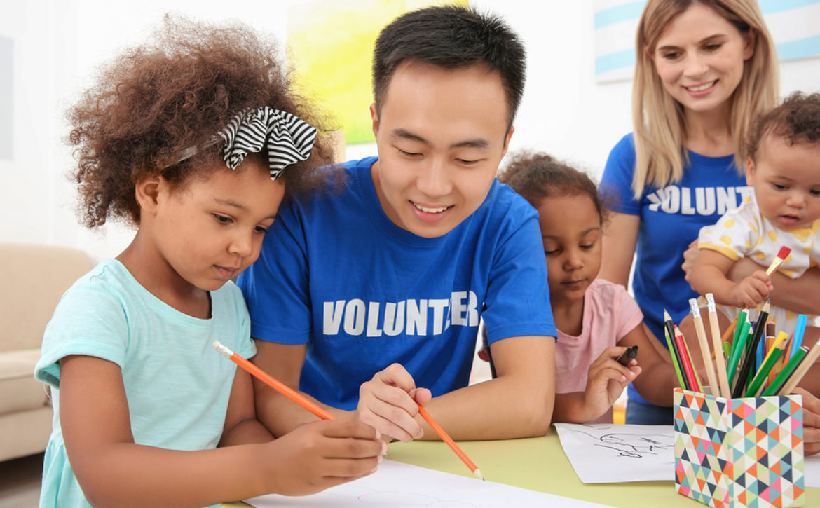 Young male volunteer drawing with little children at table. Volu