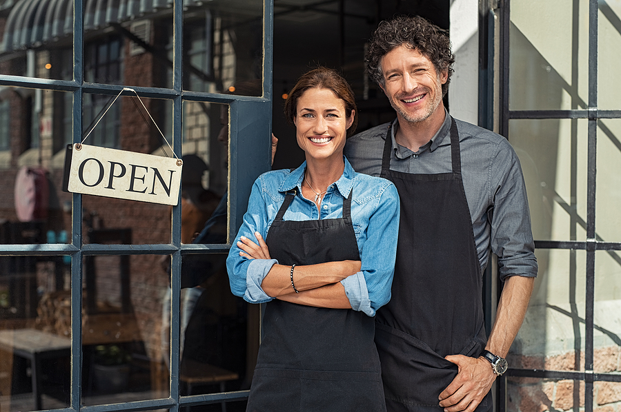 Two cheerful small business owners smiling and looking at camera